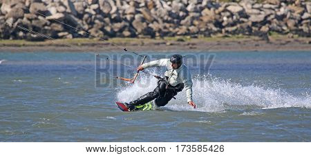 kitesurfer carving a turn onto toeside of board