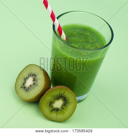 Fresh kiwi smoothie with sliced kiwi over green background