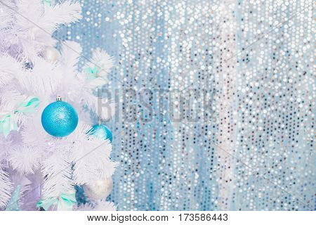 Blue Christmas toy hanging on a white spruce with snow. New Year background, New Year concept