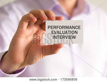 Businessman Holding A Card With Performance Evaluation Interview Message