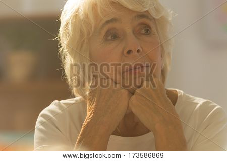 Close-up of pretty worried senior woman sitting alone