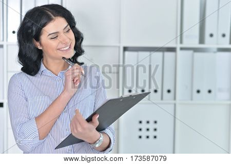 youn beautiful woman making notes using clipboard