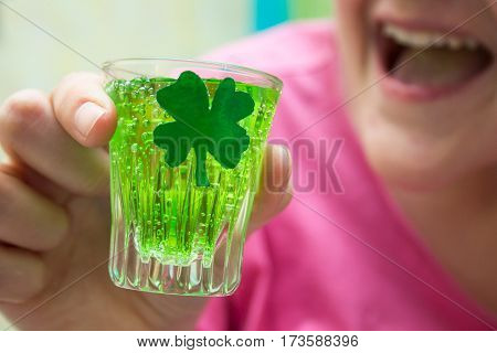 woman holding a shot of alcohol on St. Patrick's day