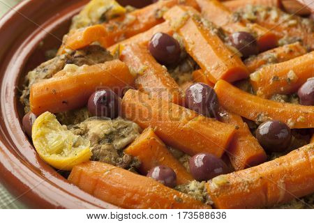 Moroccan dish with chicken, carrots, olives and preserved lemon close up