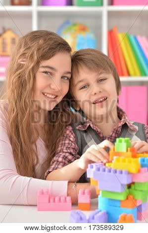 Little boy and teenage girl playing lego game togehter