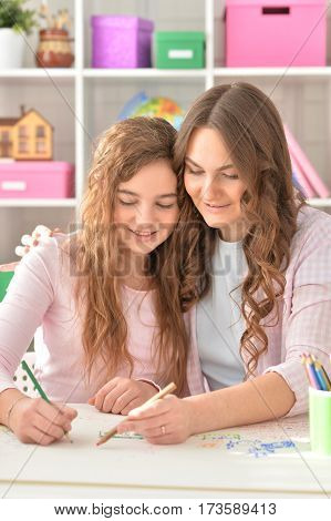 Mother and her teenage daughter drawing together at home