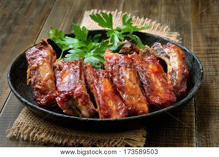 Roasted pork ribs in frying pan on wooden table
