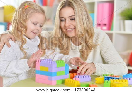 mother with little daughter making figures with constructor