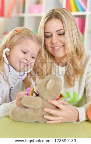 mother with little daughter playing with teddy bear, heeling it
