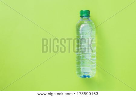 Clean drinking water in generic plastic bottle laying over green background, top view