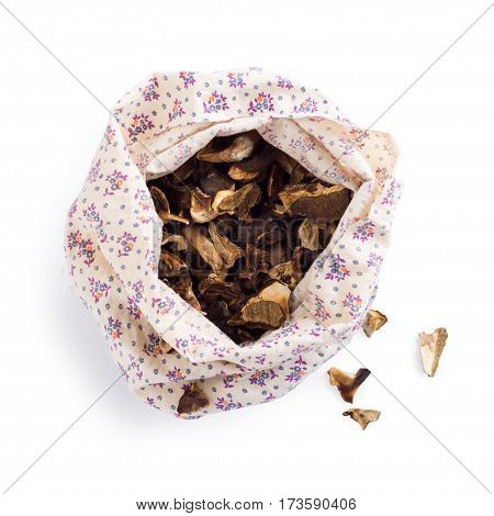 Textile bag full of dried forest mushrooms, isolated over white