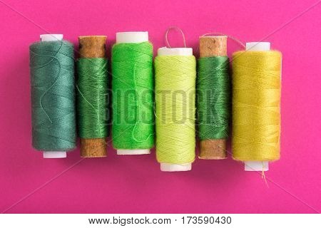 Green spools of thread over pink background, top view