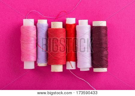 Pink spools of thread over pink background, top view