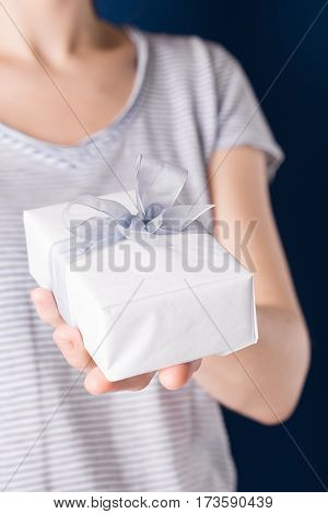 Young unrecognizable female holding gift box in a hand
