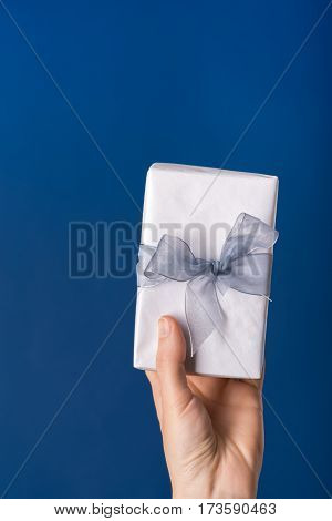 Hand holding white gift box with silver ribbon over blue background
