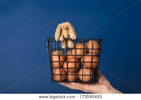 Small toy rabbit in a basket with brown chicken eggs hold on hand over blue background