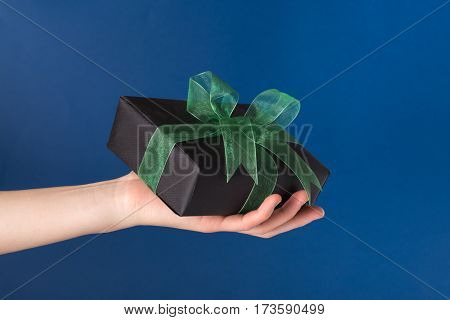 Wrapped gift box in a hand over blue background