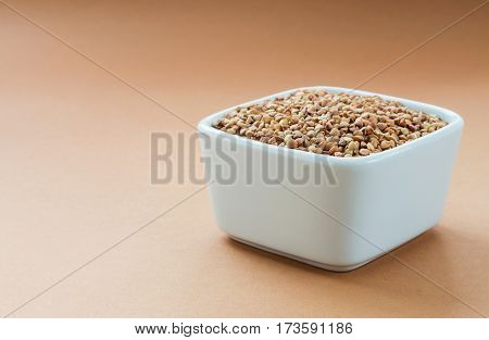 Raw organic buckwheat in white bowl on bright brown background. Superfood horizontal
