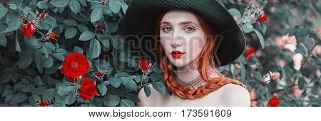 Panoramic photo of red-haired girl with blue eyes and pale skin in a green hat and dress with a red belt. Woman with long red plait against the backdrop of bush peach roses. Red lips a necklace around his neck. Bright unusual appearance. Panoramic concept