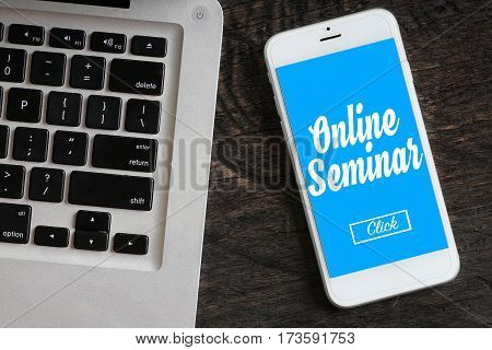 """""""Online Seminar"""" words on smartphone with a laptop near it - website multimedia and business concept"""