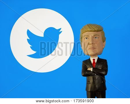 Donald Trump Bobble Head figure standing in front of a Twitter logo. Twitter is one of the favorite platforms for Trump to message