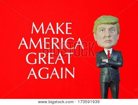 Donald Trump Bobble Head figure standing in front of a sign reading Make America Great Again, which was his campaign slogan