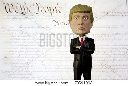 Donald Trump Bobble Head figure standing in front of the United States Constitution