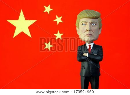 Donald Trump Bobble Head figure standing in front of a Chinese flag