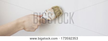 Paint brush in a man's hand on a white background . Process concept. Man painting wall illustration Man painting wall image Man painting wall concept Man painting wall website building Man painter