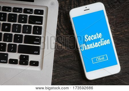 """""""Secure Transaction"""" words on smartphone with a laptop near it - website multimedia and business concept"""