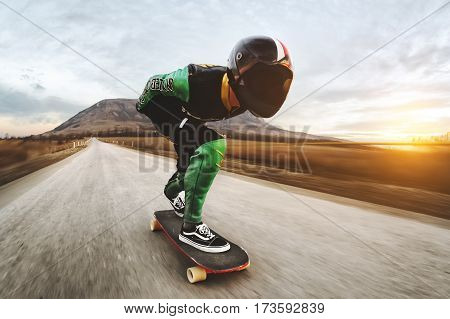 A man in a fullface helmet and a leather suit in a special rack rides a longboard on afsaltu sunset in the background mountains and beautiful sky at high speed.