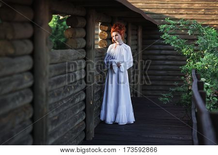 Beautiful renaissance red-haired girl with a high hair in an old white dress in the park. The Victorian era. Historic costume. White renaissance Queen. Renaissance princess castle