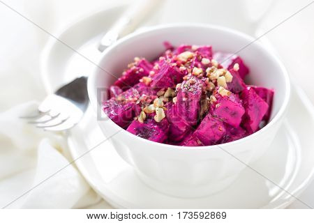 Beet vegetable salad with yogurt and walnuts in a bowl on white background