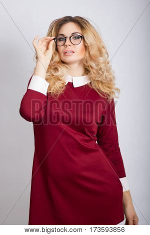 Portrait of beautiful caucasian blonde woman with curly hair standing on grey background. Young business woman with glasses looking at camera