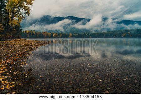 Low hanging clouds reflected in a lake.