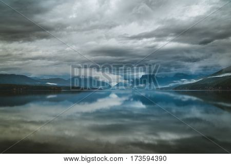 Overcast skies reflected in a calm lake.