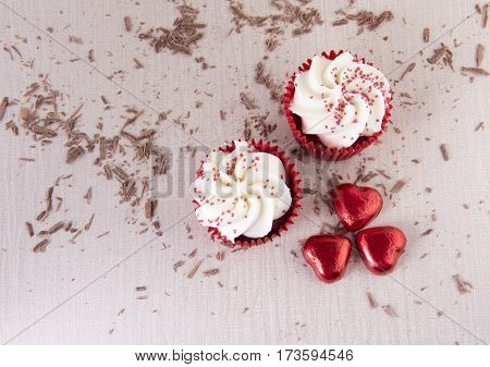 Two red velvet cupcakes surrounded by chocolate sprinkles