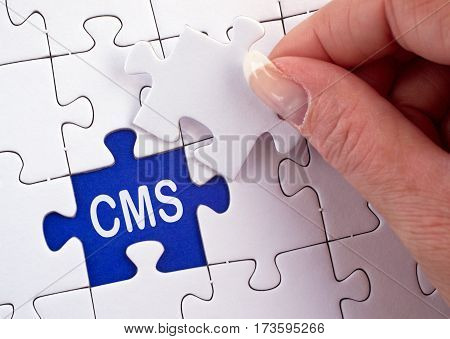 CMS - Content Management System - female hand with puzzle