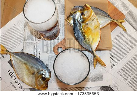 Still life with smoked fish and beer on the newspaper