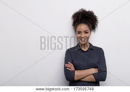 Female entrepreneur standing at wall with her arms crossed, wearing shirt