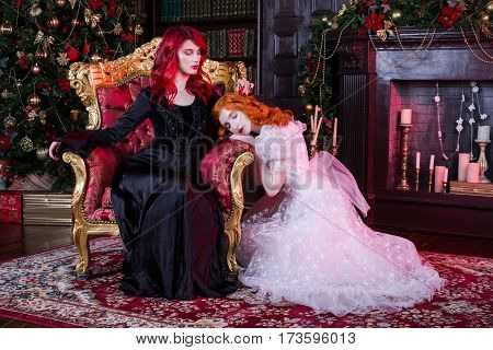 Two red-haired woman near the fireplace and the Christmas tree. Fairy and Witch. Christmas story. Boxes with gifts under a fur-tree. Candles in a candlestick. Woman in white and black dresses.