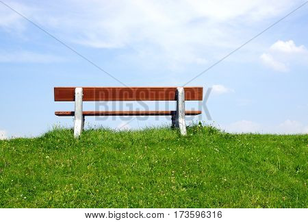 Bench in Nature with green grass and blue sky