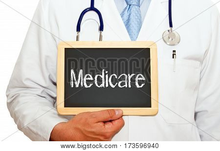 Medicare - Doctor holding chalkboard with text on white background
