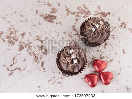 Two chocolate cupcakes surrounded by chocolate sprinkles