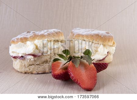 Two strawberry jam and cream scones with strawberry slices