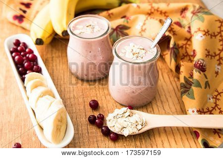 Smoothie Of Banana And Cranberries With Yogurt And Oats On An Old Table