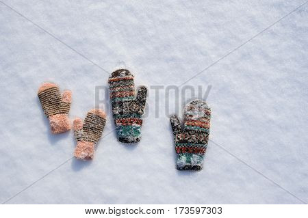 Pair of frozen mittens on the snow