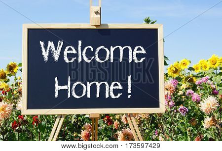 Welcome Home - easel in the summer garden with flowers