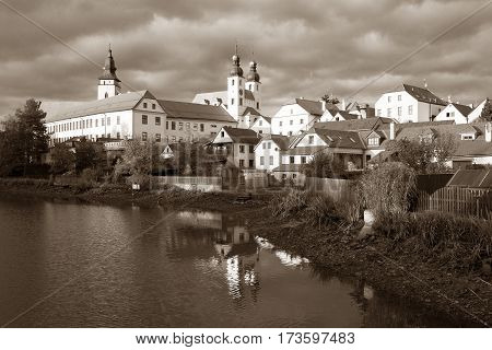 Sepia colored view of Telc or Teltsch town mirroring in lake World heritage site by unesco in Czech Republic