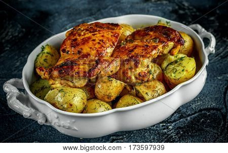 New boiled potatoes with dill and butter served with baked skinless boneless chicken thighs in vintage casserole.